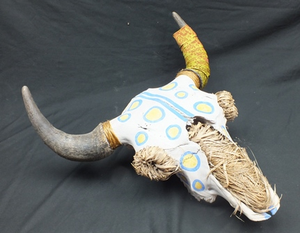 A Southwest USA steer skull with horns, painted decoration and straw detail, 51cm wide