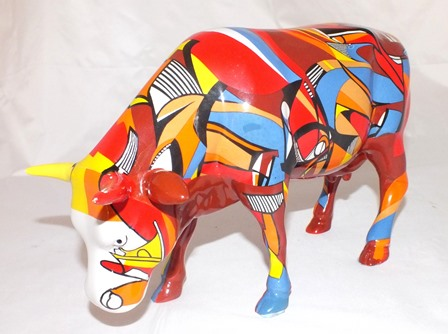 An early 21st century glazed ceramic cow figure, brightly coloured, from the Cow Parade series, 16cm high illustrated