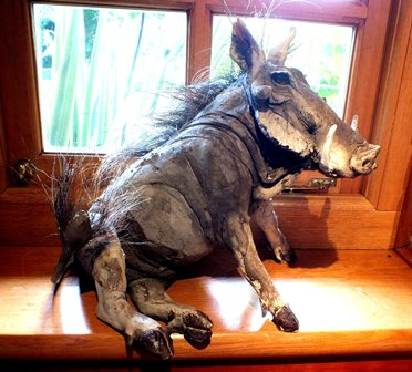 Nick Mackman  A late 20th century glazed Raku-fired warthog, seated on his haunches, with applied hair to back and tail tip, 36cm high