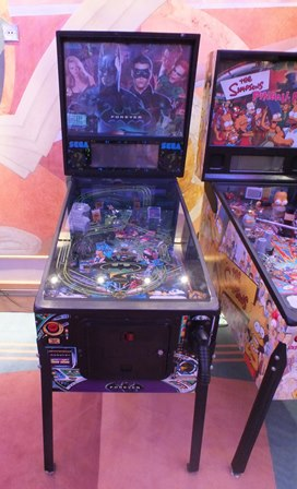A Sega Batman Forever pinball machine, with pistol handle trigger and scoreboard back, 63cm wide, 132cm deep, raised on metal supports