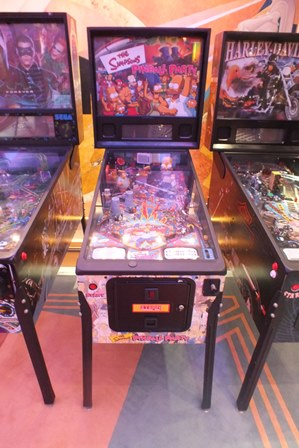A Stern Pinball Inc. The Simpsons Pinball Party pinball machine, with scoreboard back, raised on metal supports, 56cm wide, 131cm deep