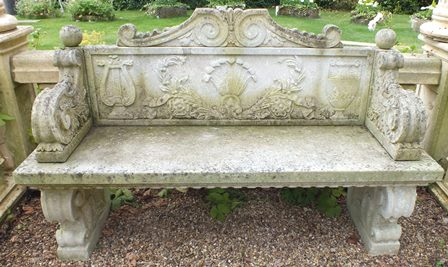 A pair of reconstituted stone classical form benches, to the back a double scrolled pediment over a panel depicting a lyre, vase and feathers, scroll arms and feet, 159cm wide, 96cm high illustrated