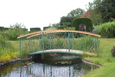 A 20th century craftsman made single span arched bridge of bound reed and bulrush design, having hardwood planks and moulded profile hand rails, span approx 6m width 1.37m overall length 6.4m (manufactured by Cotswold Decorative Ironworks) illustrated