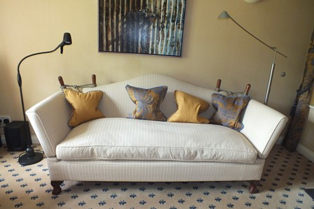 A two-piece suite in the Knole style, comprising hump backed three-seater settee, and single deep seated armchair, having neutral geometric upholstery and supported on stubby cabriole legs terminating in ball and claw feet