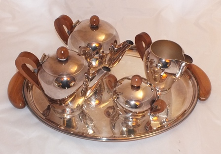 A four-piece silver plated tea set on an oval tray, produced by Alessi, in the Bombe pattern, having apple wood handles and knobs