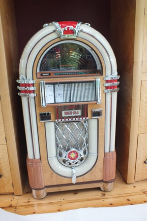 A Rock-ola juke box, manufactured by Antique Apparatus - Stereo Juke Boxes of Torrance, California (see labels verso), having arch top and sapele mahogany sides, chrome effect grilles, serial no.184901, model no.CD-8, 83cm wide, 1.55m high  illustrated