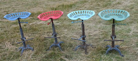 A set of four tractor seat bar stools, the painted cast iron seat on a screw adjustable support, with foot rest and four splayed feet