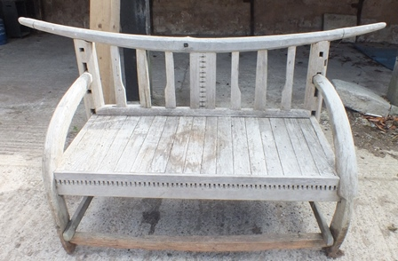 A rustic garden bench, having carved bow back, with arched arms and planked seat, 1.76m wide, centre height, 83cm
