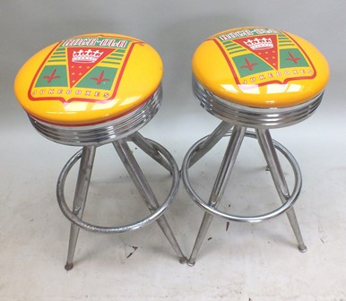 A pair of Rock-ola bar stools, having printed tops on chromed bases, revolving tops read Rock-ola jukeboxes