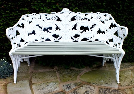 A 19th century Coalbrookdale cast iron bench of fern  and blackberry design with wooden slatted seat, 154cm wide illustrated