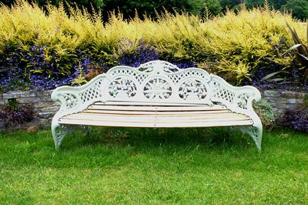 A Victorian cast iron garden bench, of scrolling form with bound reed arms, acanthus leaf crest, fern, rose and pea panels, within a trellis frame in pale green 196cm wide illustrated