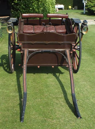 A 19th century two wheel horse drawn trap, in brown red and gold line livery, padded cushion seat, solid rubber tyres, complete with a pair of coach lamps and protective cover illustrated