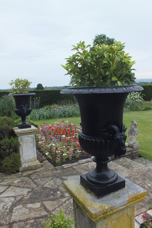 A pair of 18th century design bronze garden urns with egg and dart rims, fluted bases on socle stems to a square platform with twin decorative handles, 65cm high x 48cm diameter to top x overall 142 cm high