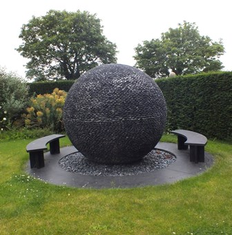 David Harber A 20th century garden water feature entitled Dark Planet being a sphere of black pebbles set in a circular bed of pebbles, surrounded by slate slabs supporting two demi-lune slate benches, sphere approx 2m diameter, outer diameter ofslate surround approx 3.6m, with underground tank, pumps for the water cascade and having interior fibre optic lighting with numerous pin hole surface light heads  illustrated