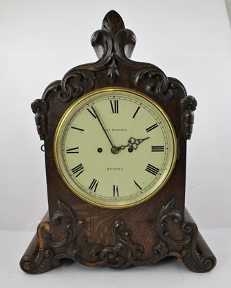 CHAS. DESPREZ - BRISTOL A VICTORIAN OAK AND SIMULATED ROSEWOOD BRACKET CLOCK, having foliate moulded ornate applied front, cast brass bezel, re-painted dial, 8-day two-train English double chain fusee mechanism and gong strike, 54cm high x 44cm wide x 19cm deep