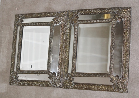 A PAIR OF LATE 19TH CENTURY EMBOSSED BRASS FRAMED CUSHION FORM WALL MIRRORS, 38cm x 32cm