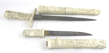 A JAPANESE TANTO (knife or dagger) Meiji period (1868-1912), elaborately overall carved ivory handle and scabbard, the handle with birds amidst blossoms, the scabbard with figures at work in a stylised landscape believed to be tea picking and leaf drying.  The scabbard is missing the Kogatana (small utility knife) which would have fitted into the outside of the scabbard, overall length 29cm, blade length 19cm