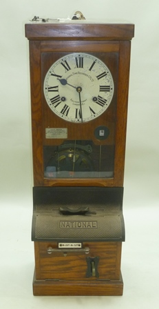NATIONAL TIME RECORDER CO LTD, AQUINAS STREET, LONDON, SE1. An oak cased factory Time Clock with painted enamel dial and keys, 1m high