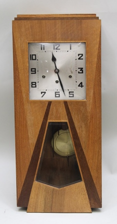 AN ART DECO CASED DROP DIAL WALL CLOCK with optional quarter chimes, the case 74cm x 32cm, with pendulum and key