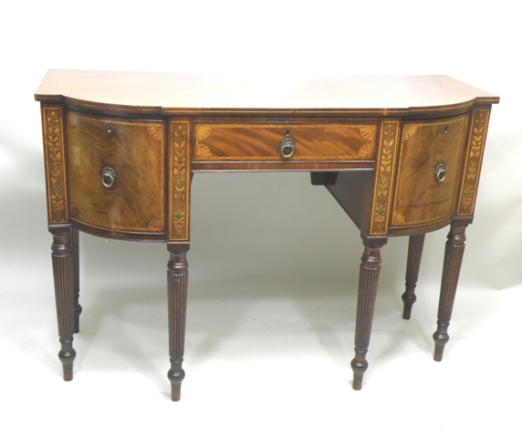 A REGENCY MAHOGANY SIDEBOARD, having re-entered inverted D-shaped top with later boxwood strung and satinwood inlaid surround, over a single frieze drawer flanked by twin deep drawers with provision for another drawer below, raised on turned taperedand reeded legs, 96cm high x 1.5m wide