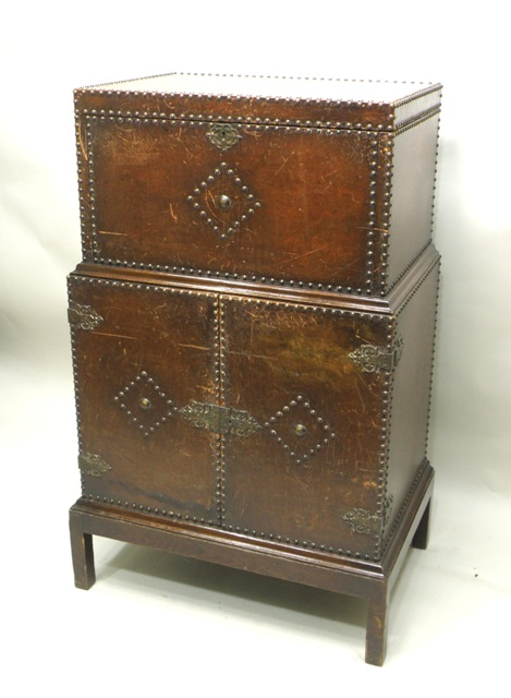 A MAPLE & CO 1930'S OAK AND LEATHER COCKTAIL CABINET, having lift up lid revealing a fitted interior with Maple & Co EPNS waiter, the base with two cupboard doors revealing fitted cellaret, 117cm high x 71cm wide