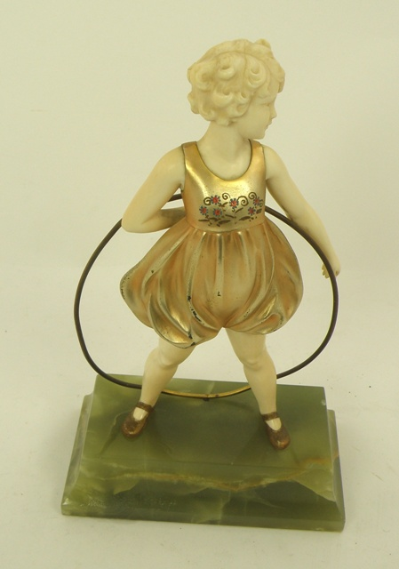 FERDINAND PREISS Hoop Girl, a cast bronze gilded and ivory figure, the girl with flowers on her smock, on original onyx plinth, signed, 20.6cm high