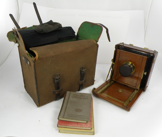 J.T. CHAPMAN THE BRITISH AN EARLY 20TH CENTURY MAHOGANY AND BRASS MOUNTED THORNTON PICKARD STYLE PLATE CAMERA with bellows, a Ross of London 220mm brass bound lens, a period canvas and leather strapped holdall, a Thornton Pickard patent mahogany shutter application in original box, and three period mahogany plate carriers