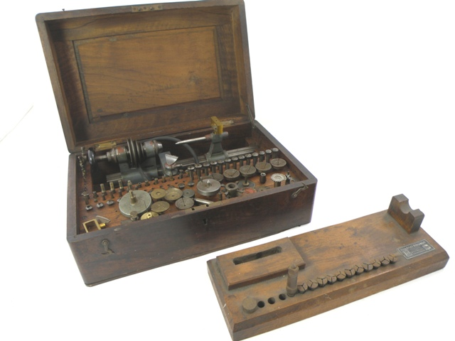 AN EARLY 20TH CENTURY FRIEDRICH SCHUBERT WATCHMAKER'S LATHE in period mahogany box, with an extensive set of collets, chucks and other attachments, a wooden plinth, etc