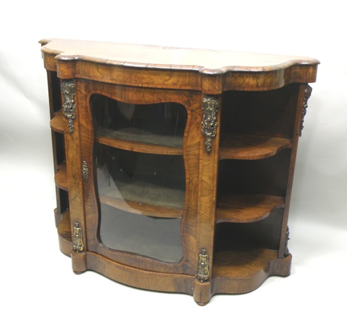 A VICTORIAN WALNUT CREDENZA having a figured demi veneered and shaped top with moulded edge over a central glazed door with figured surround, flanked by uprights with ormolu capitals, twin three-tier open sides, on a plinth base
