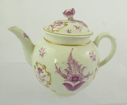 A GEORGE III PERIOD WORCESTER PORCELAIN BULLET FORM TEAPOT with hand painted puce floral decoration, some constrained to gilded cartouches, the cover with floral knop, circa 1800, overall 14cm high