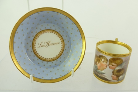 AN EARLY 19TH CENTURY BERLIN (KPM) PORCELAIN COFFEE CAN AND SAUCER with hand painted panel of winged putti, pale blue ground with gilded stars, sole of saucer gilt inscribed Les Heureux (the Happy), can is 8cm high with hand painted cobalt blue sceptre mark to base