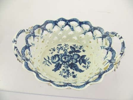 AN 18TH CENTURY WORCESTER TWIN HANDLED PORCELAIN CHESTNUT BASKET of reticulated form, with applied flower heads and printed in cobalt blue with the pine cone pattern, hatched blue crescent mark to base, circa 1770, 19cm wide handle to handle
