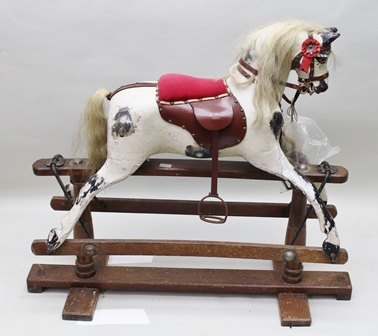 AN EARLY TO MID 20TH CENTURY CARVED WOOD, GESSO AND PAINTED ROCKING HORSE with horse hair mane and tail, leather harness, on trestle frame stand, 97cm high