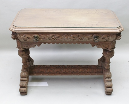 A 17TH CENTURY DESIGN OAK CENTRE/HALL TABLE having canted top, fitted single frieze drawer with brass handles, raised on cup and cover trestle end supports with under frame, raised on Dolphin mask feet, 106cm x 64cm