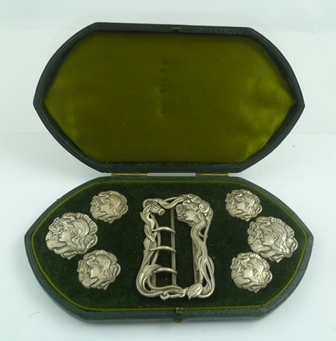 E. MANDER AND SON AN EDWARDIAN ART NOUVEAU SET OF BUTTONS AND BUCKLE, cast silver, decorated with profile portraits of young women, Birmingham 1902, in original vendors green leather case, silk and velvet lined