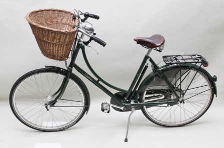 A PASHLEY SOVEREIGN 5-SPEED LADYS UPRIGHT BICYCLE, finished in British Racing Green, with woven wicker shopping basket, dynamo powered front and rear lights, immobiliser and pannier rack, having a traditional Brookes sprung seat with 22 internal diameter spoked wheels