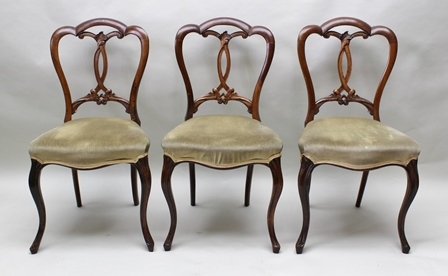 A SET OF SIX CROWN BACK VICTORIAN WALNUT SINGLE DINING CHAIRS having splat backs, pale green fabric upholstered stuff over serpentine fronted seats, raised on cabriole fore supports