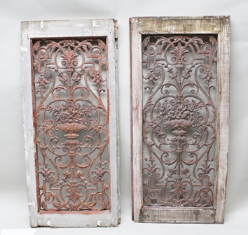 A PAIR OF VICTORIAN CAST IRON GRILLES, of scrolling form with acanthus leaves, bell husks and central urns of flowers, remains of pink/red paint, mounted in plain wooden frames, grilles 119cm x 49cm