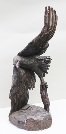 PREDATOR AND PREY a carved wood sculpture of a swooping eagle with fish prey in talons, 105cm high