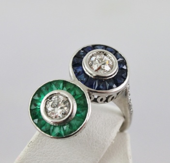 A RHODIUM FINISHED WHITE GOLD COLOURED METAL CROSSOVER RING having two head top each with a brilliant, surrounded by calibre cut emeralds and sapphires, rub-over set diamond shoulders and plain shank, size N