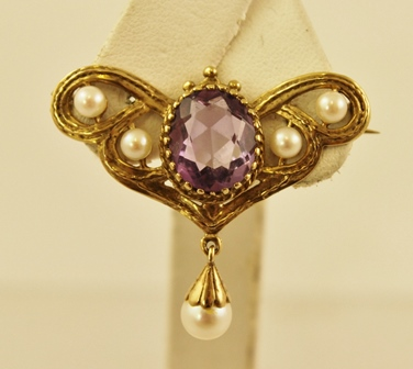 A VICTORIAN STYLE GOLD COLOURED METAL LAPEL BROOCH set with oval amethyst and five cultured pearls
