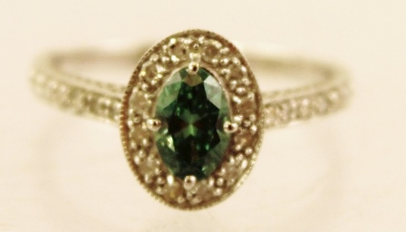 A RHODIUM FINISHED 18CT WHITE GOLD DIAMOND DRESS RING the centre stone an oval marquise cut green diamond bordered by twelve 8/8 cuts, diamond shoulders and tooled shank, size M1/2