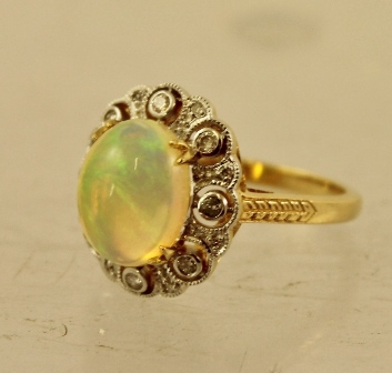 AN OPAL AND DIAMOND CLUSTER RING having cabochon claw set central stone with eight individually suspended diamonds around, in white and yellow gold coloured metal, size M1/2