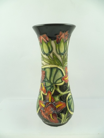 A MOORCROFT WAISTED VASE, circa 1999, having stylised flower and veined leaf design, on an ebony ground, impressed and painted factory marks to base, 21cm high