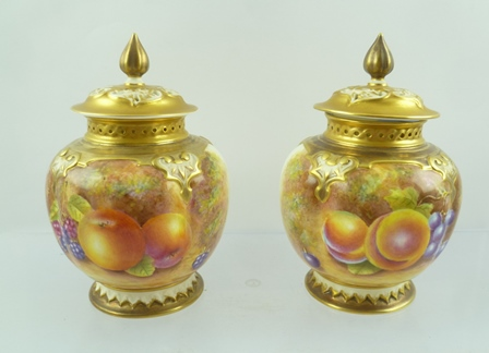 A PAIR OF ROYAL WORCESTER PORCELAIN POT POURRI VASES of globular form with pierced covers, hand painted fruit designs, signed Leaman, 13cm high