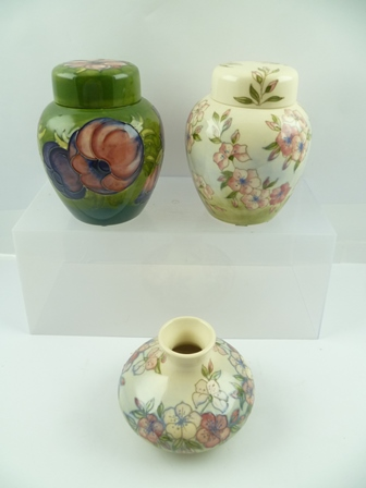 A MOORCROFT GINGER JAR AND COVER, Clematis pattern, on green ground, 15cm high, together with an Apple Blossom pattern ginger jar with cover, and an Apple Blossom squat vase, each with impressed and painted factory marks to base (3)