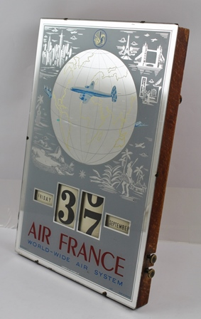 A MID 20TH CENTURY AIR FRANCE DATE INDICATOR WALL MIRROR, printed with aircraft, globe and world features, inscribed Air France World-wide Air System, 36cm x 24cm