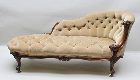 A LATE VICTORIAN MAHOGANY SHOW-WOOD  FRAMED CHAISE LONGUE, decoratively carved scrolling detail, shaped single end button back and seat, upholstered in cream/fawn fabric, on cabriole supports with ceramic castors