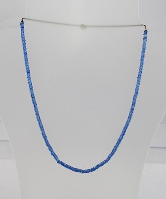 AN EARLY 20TH CENTURY CEYLON SAPPHIRE NECKLET, comprising multiple faceted stones in cornflower blue with gold coloured metal chain and bolt ring and clasp