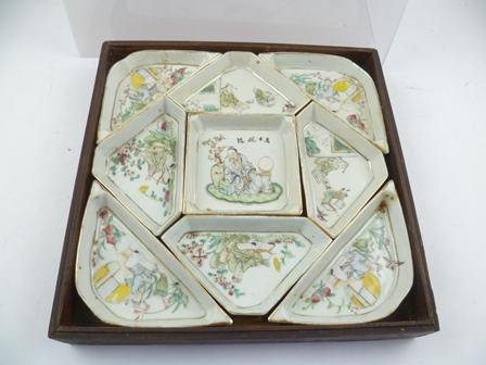A CHINESE FAMILLE VERTE SET OF PORCELAIN HORS DOEUVRES DISHES, painted with scholars in studio and garden settings, painted character marks to central dish, overall the dishes form a 27cm square shape, stored within a stained wood box